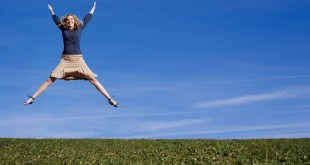 A pretty woman jumps for joy in a field